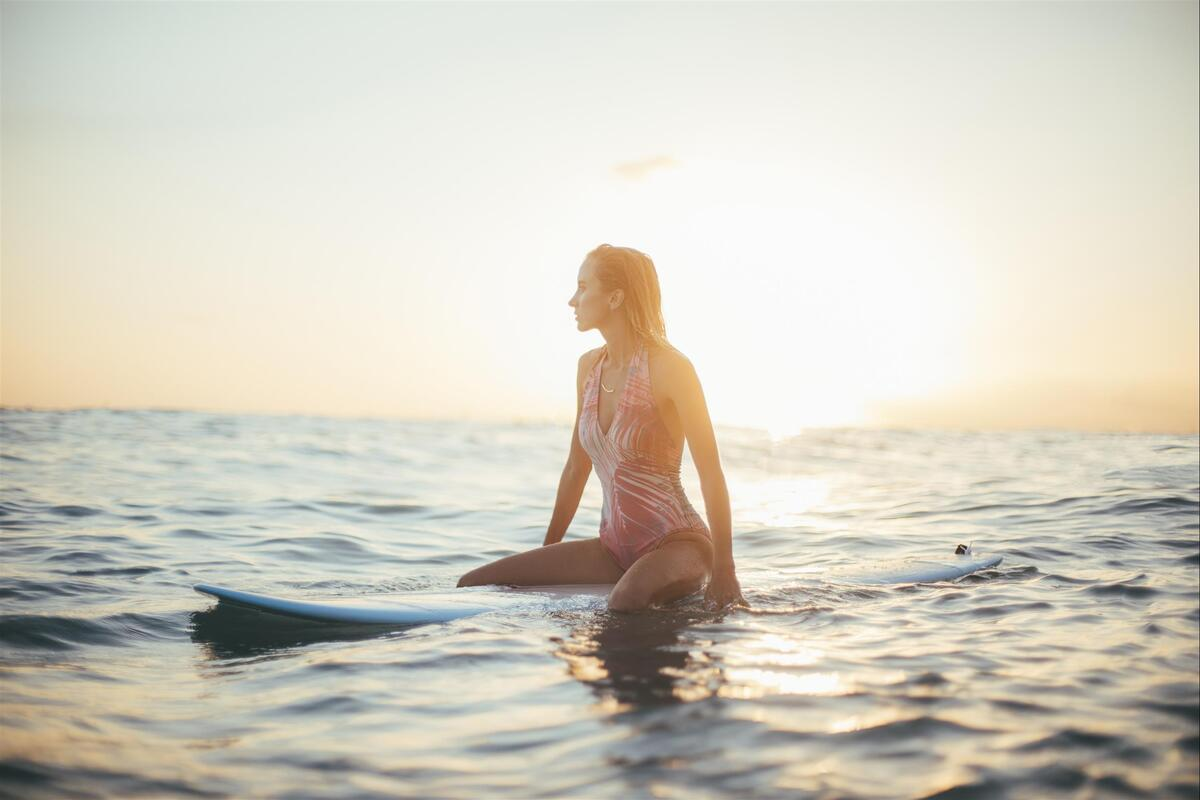 girl sitting on surfboard